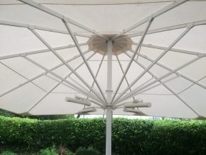 Giant white umbrella in garden with heaters, alfresco lifestyle weather protection