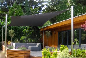 Photo of mesh fabric garden shade sail with stainless steel posts over deck with sofas and timber built man cave/log cabin