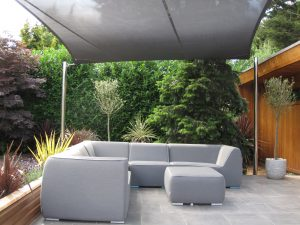 Outside sofas under garden shade sail, on a deck designed and installed by Alfresco365