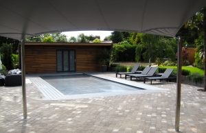 Photo showing view form under the 3d hypar garden shade sail overlooking a swimming pool