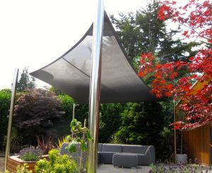 Close up of the underside of a mesh garden shade sail with stainless steel posts.