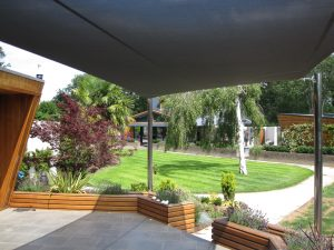 view of garden from a terrace covered by a garden shade sail, cool alfresco lifestyle