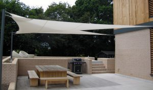 pair of layered white shade sail triangles fitted to chic modern home, alfresco lifestyle a la mode